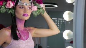 Donna con i fiori ed il trucco luminoso video d archivio