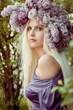 Donna con i fiori lilla Fotografia Stock