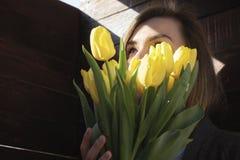 Donna con i fiori in una stanza scura fotografie stock libere da diritti