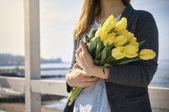 Donna con i fiori vicino alla riva di mare immagine stock