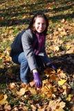 Donna con i fogli in autunno fotografie stock libere da diritti