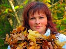 Donna con i fogli di autunno Fotografie Stock