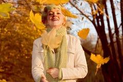 Donna con i fogli di caduta Fotografia Stock Libera da Diritti
