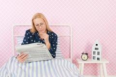 Donna con i giornali a letto immagini stock libere da diritti