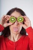 Donna con i kiwi affettati sugli occhi e sull'attaccare fuori lingua Immagini Stock