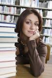 Donna con i libri che si siedono allo scrittorio delle biblioteche Immagini Stock Libere da Diritti