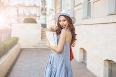 Donna con i libri coperti in bianco che sbatte le palpebre e che indica su voi Fotografie Stock