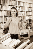 Donna con i libri d'acquisto della ragazza Immagine Stock