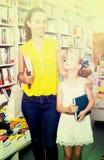Donna con i libri d'acquisto della ragazza Fotografia Stock Libera da Diritti