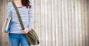 Donna con i libri e borsa contro il pannello di legno confuso Immagini Stock