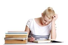 Donna con i lotti dei libri che studia per gli esami. Fotografia Stock