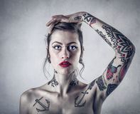 Donna con i lotti dei tatuaggi Immagini Stock