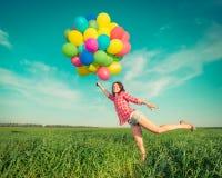 Donna con i palloni del giocattolo nel giacimento di primavera Fotografie Stock Libere da Diritti
