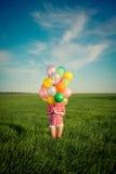 Donna con i palloni del giocattolo nel giacimento di primavera Immagini Stock Libere da Diritti