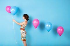 Donna con i palloni nello studio su un fondo blu immagine stock libera da diritti