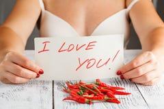 Donna con i peperoncini rossi roventi sulla tavola Immagini Stock Libere da Diritti