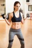 Donna con i pesi di sollevamento dell'ABS alla palestra Fotografia Stock Libera da Diritti