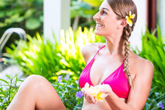 Donna con i petali del fiore in giardino tropicale allo stagno Immagini Stock Libere da Diritti