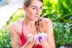 Donna con i petali del fiore in giardino tropicale allo stagno Fotografia Stock