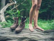 Donna con i piedi nudi sull'albero caduto in foresta Fotografie Stock Libere da Diritti
