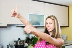 Donna con i pollici su in cucina Fotografia Stock