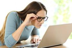 Donna con i problemi di vista da leggere sulla linea contenuto immagine stock