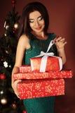 Donna con i regali di Natale lunghi della tenuta dei capelli scuri Immagine Stock