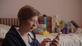 Donna con i regali sui precedenti facendo uso dello smartphone alla compera online video d archivio