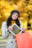 Donna con i sacchetti della spesa e la compressa in autunno Fotografia Stock