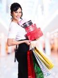 Donna con i sacchetti della spesa e le scatole di colore. Fotografie Stock