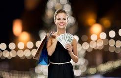 Donna con i sacchetti della spesa ed i soldi a natale Fotografia Stock