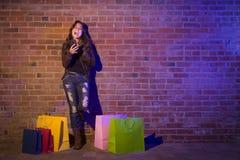 Donna con i sacchetti della spesa facendo uso del telefono cellulare contro il muro di mattoni Fotografia Stock