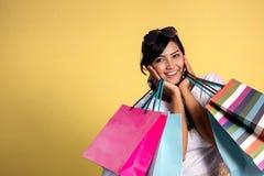 Donna con i sacchetti della spesa sopra fondo giallo fotografia stock libera da diritti