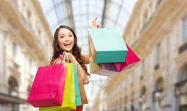 Donna con i sacchetti della spesa sopra il fondo del centro commerciale immagini stock libere da diritti