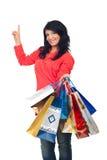 Donna con i sacchetti di acquisto che indica in su Fotografie Stock Libere da Diritti