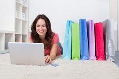 Donna con i sacchetti di acquisto e la carta di credito Fotografia Stock Libera da Diritti