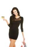 Donna con i sacchetti di acquisto e la carta di credito Fotografia Stock
