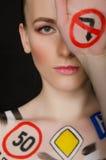 Donna con i segnali stradali dipinti Fotografie Stock Libere da Diritti
