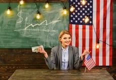 Donna con i soldi del dollaro per il dono Riforma americana di istruzione alla scuola nel 4 luglio Pianificazione di reddito dell Fotografia Stock
