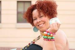 Donna con i soldi rossi della holding dei capelli ricci Fotografia Stock Libera da Diritti