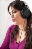 Donna con i telefoni dell'orecchio Immagini Stock