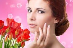 Donna con i tulipani rossi freschi del bello giardino Fotografia Stock Libera da Diritti