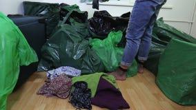 Donna con i vestiti della seconda mano vicino ai sacchetti di plastica video d archivio