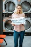Donna con i vestiti rivestiti di ferro nella lavanderia immagini stock