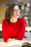 Donna con i vetri in biblioteca nei pensieri Immagine Stock