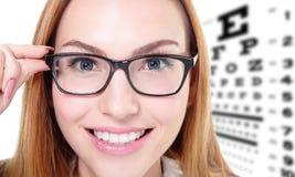 Donna con i vetri ed il grafico di prova dell'occhio Fotografie Stock