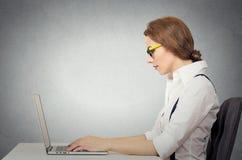 Donna con i vetri facendo uso del suo computer portatile Fotografia Stock Libera da Diritti