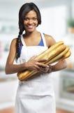 Donna con il baguette quattro nella cucina Fotografia Stock