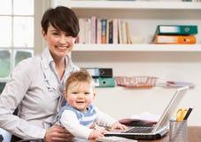 Donna con il bambino che lavora dalla casa fotografia stock