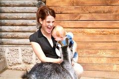 Donna con il bambino che picchietta la capra allo zoo Fotografia Stock Libera da Diritti